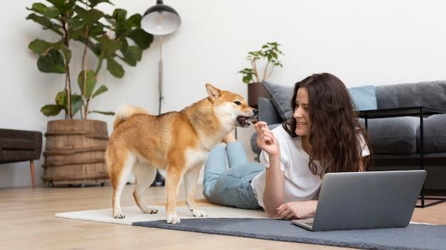Donna che cerca di lavorare con il suo cane in giro