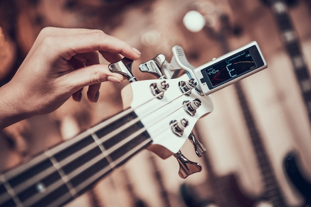 Woman tunes guitar with tuner clip twisting on fretboard.