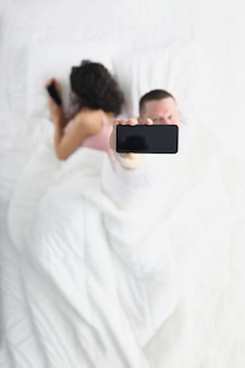 Woman turning away hides smartphone screen from her husband while lying on bed husband watches her using application from his smartphone