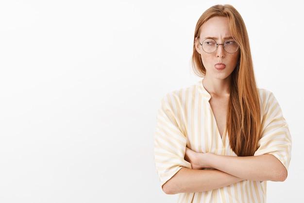 Женщина поворачивает глаза влево, прищуриваясь, высунув язык от неприязни, скрещивая руки на груди, стоя в заблокированной позе