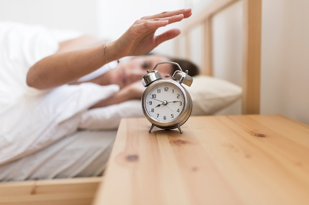 Woman turning off alarm clock while lying on bed
