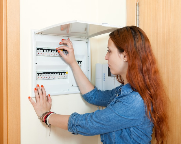 Woman turning off the light-switch
