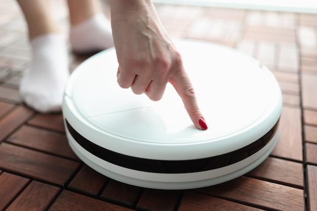 Женщина, поворачивая палец крупным планом робота-пылесоса