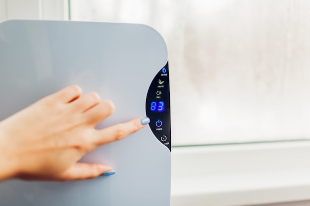 Woman turns dehumidifier on using touch panel by wet window.
