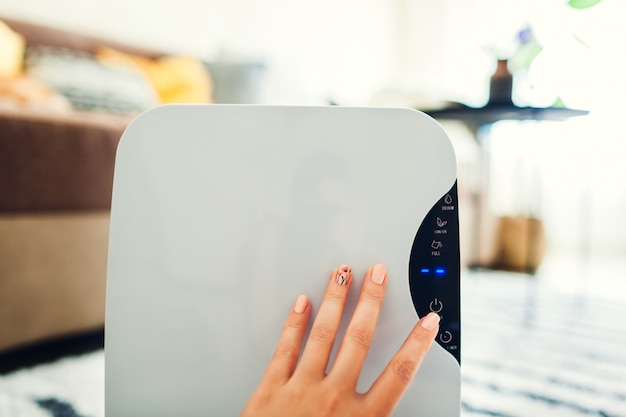 Woman turns dehumidifier on using touch panel at home. modern airdryer device for cleaning air