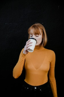 Woman in a turtleneck drinking from a takeout paper cup mockup