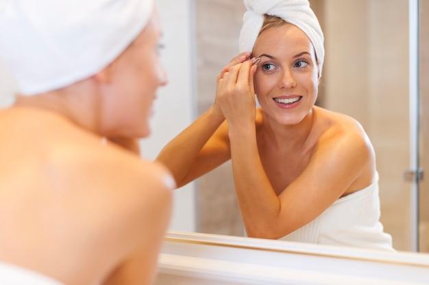 Женщина выщипывает брови перед зеркалом