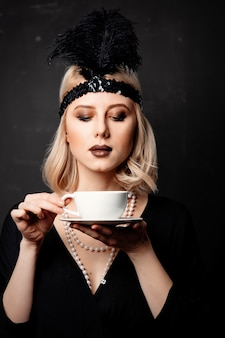Woman in twenties years clothes with cup of coffee