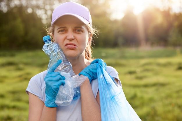 女性は顔をねじり、使用済みのペットボトルとゴミ袋を持って、公園の片付けに疲れていて、廃棄物の再利用を呼びかけ、環境を汚染していません。