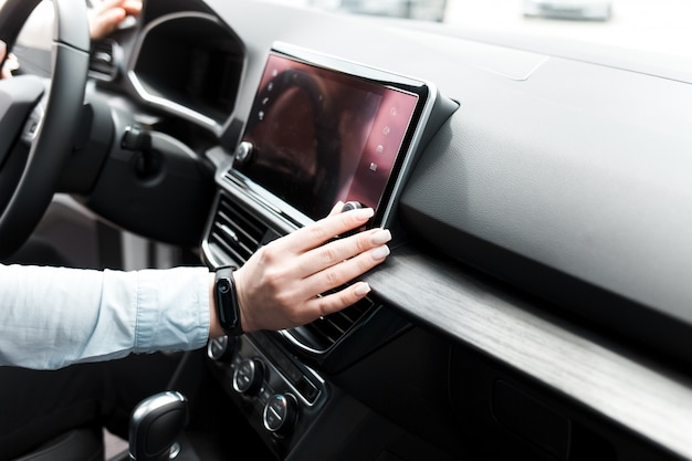 Woman twists the controls on the car radio.