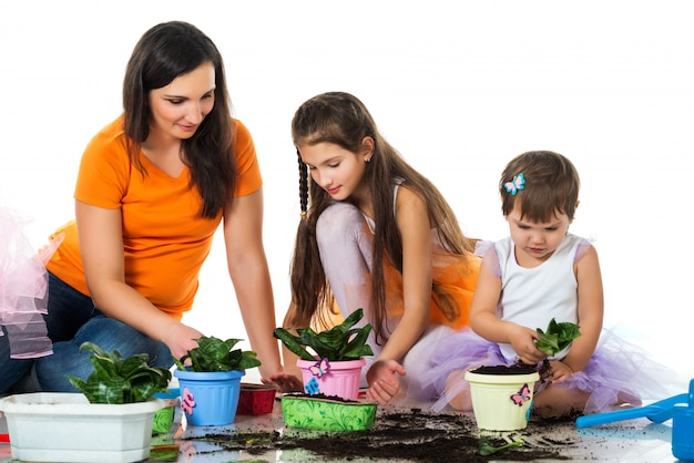 Woman and two girls plant flowers in flowerpots