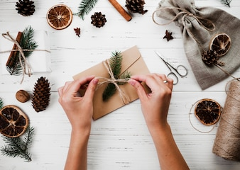 Woman tying band on Christmas envelope
