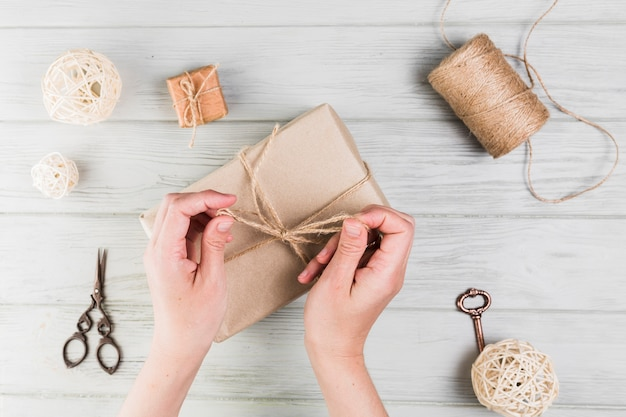 Woman tying gift box with string on textured wooden surface