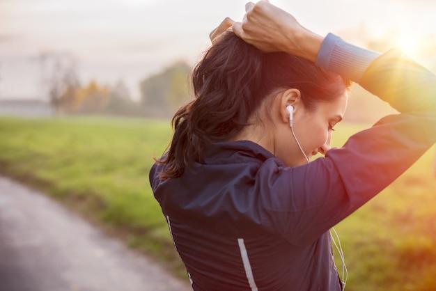 Женщина, завязывающая волосы в хвост, готовится к тренировкам на закате