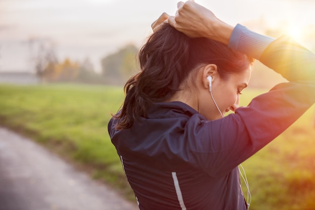 Woman tying hair in ponytail getting ready for exercising at sunset