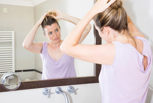 Woman tying her hair looking at mirror in the bathroom
