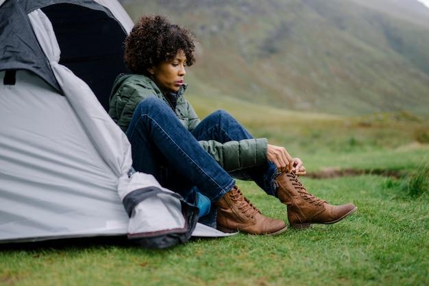 彼女のテントで彼女の靴ひもを結ぶ女性