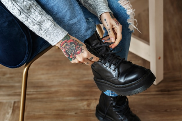 Woman tying her shoelaces on a chair Premium Photo