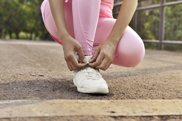 Woman tying her shoelaces. prepare for workout outdoor
