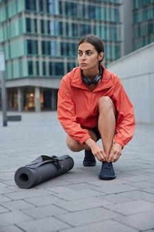 훈련 전에 운동화 끈을 묶는 여성은 필라테스를 준비하거나 운동복을 입고 달리기를 하고 야외에서 blured에 맞서 포즈를 취합니다.