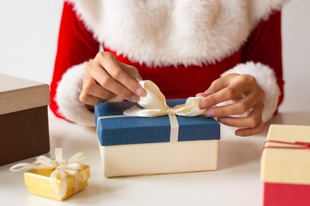 プレゼントボックスの上にリボンを結ぶ女