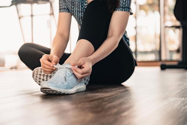 Женщина связывает кроссовки на полу в тренажерном зале фитнеса
