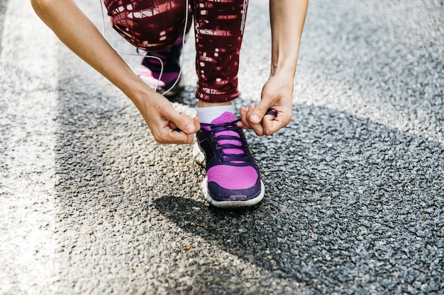Woman tying running shoes on road
