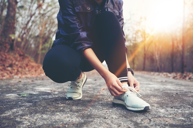 Woman tying shoe laces for sport fitness runner getting ready for jogging outdoors