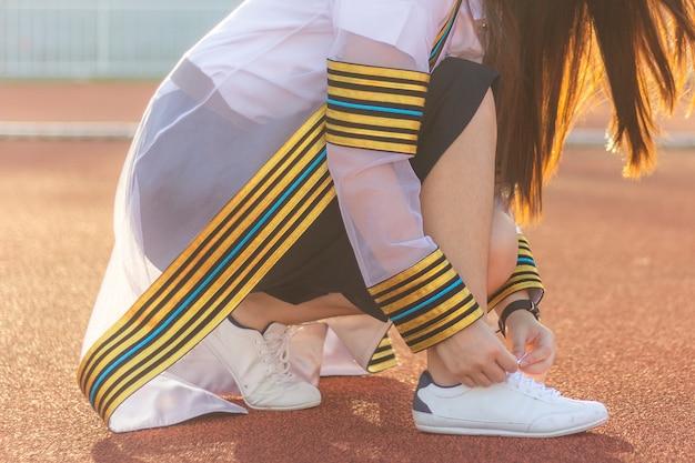 ファッショナブルな流行に敏感なスニーカーの靴ひもを目標にランニングトラックで開始する前に結ぶ女性