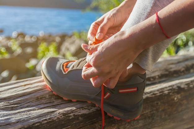 森の中で靴紐を結ぶ女性