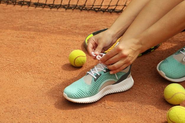ラケットとテニスボールで粘土のコートに靴ひもを結ぶ女