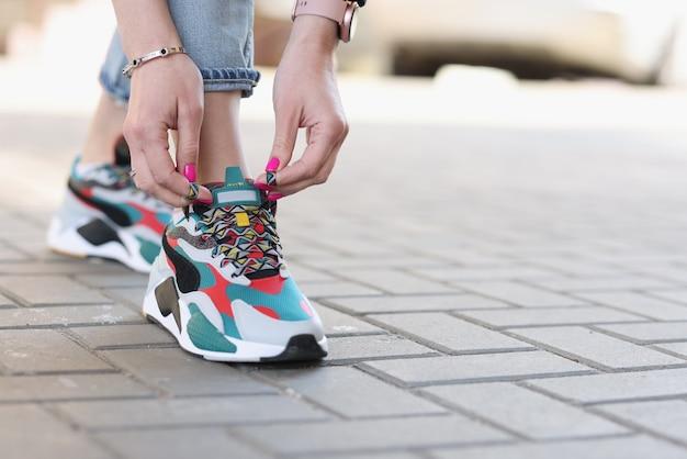 スポーツスニーカーのクローズアップで靴紐を結ぶ女性