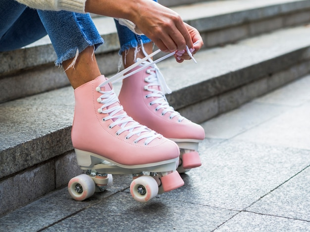 Woman tying shoelaces on roller skates with copy space