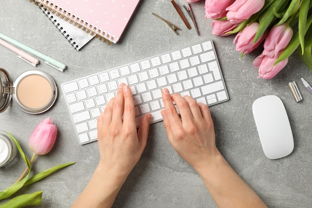 Woman types keyboard on grey background with tulips, top view