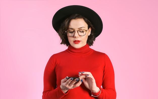 携帯電話でメッセージを入力する女性は喜ぶ。ピンクの壁にメガネの女性が電話の画面を見ています。