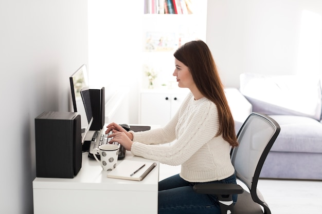 Woman typing at computer at home