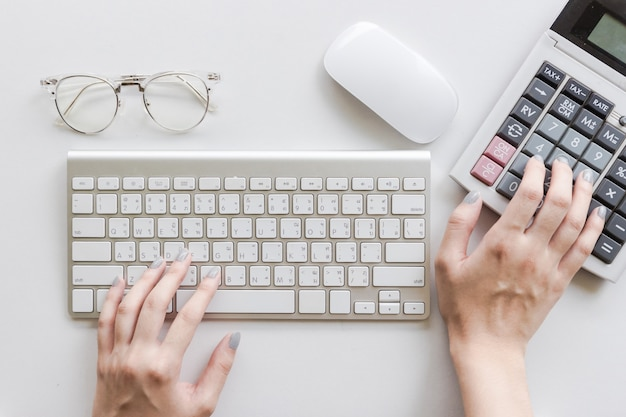 Woman typing on the keyboard, using calculator, glasses and mouse