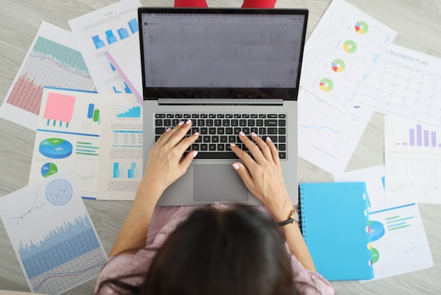 Woman typing on laptop keyboard among set of documents top view