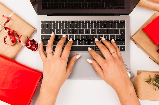 Woman typing on laptop with christmas boxes on table