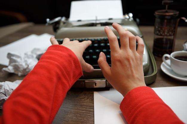 Woman typing on old typewriter at table