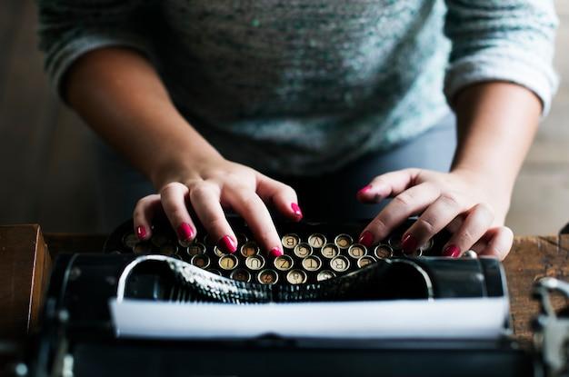 Женщина, набрав на старинной пишущей машинке на деревянном столе