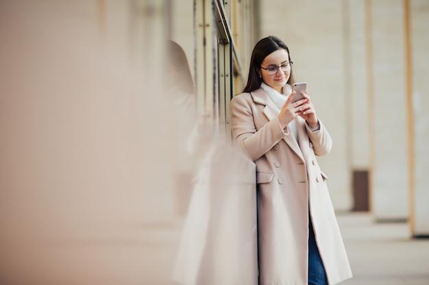 パノラマの窓に対して電話でテキストを入力する女性