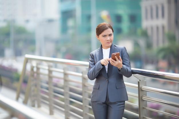 Женщина печатает смартфон, и она злится