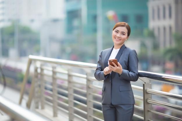 スマートフォンを入力する女性と彼女は幸せを感じる