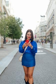 通りを歩いて携帯電話で入力する女性