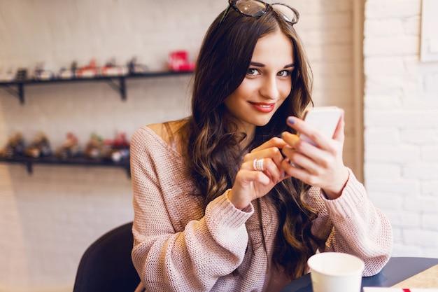モダンなカフェでスマートフォンで書き込みメッセージを入力する女性。携帯電話を使用してコーヒーやカプチーノのテーブルに座っている若いきれいな女の子の画像をトリミングしました。