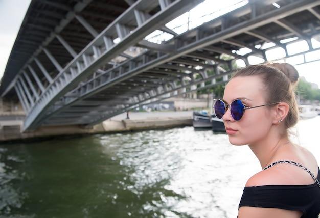 Женщина под мостом в париже, франция. девушка в синих очках на берегу реки. ориентир и концепция осмотра достопримечательностей. летние каникулы и путешествия. концепция путешествия