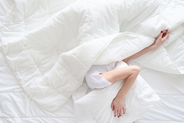 Женщина под одеялом накрыла голову подушкой, вид сверху. концепция шумных соседей