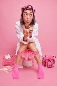 女性はトイレで美容トリートメントを受けます目の下にヘアローラー保湿パッチを適用します爪を磨きます特別な機会のために準備しますトイレに座ってバスローブを着ます