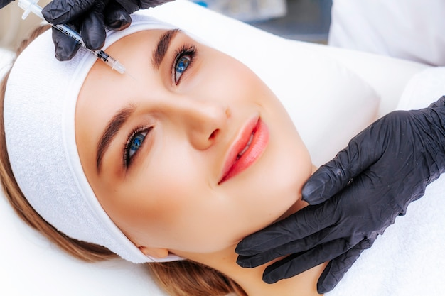 A woman undergoing a facial bioreinforcement procedure at a beautician. rejuvenation and treatment of wrinkles.